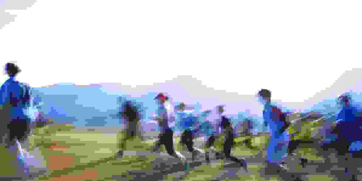 Ein unscharfes Bild, auf dem Läufer in der Natur zu sehen sind.