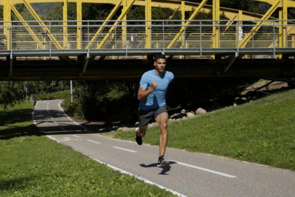 Ein Läufer läuft unter einer gelben Brücke hindurch.