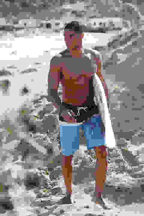 Ein Mann mit Surf-Badeshorts am Strand. Unter dem Arm trägt er ein Surfbrett.
