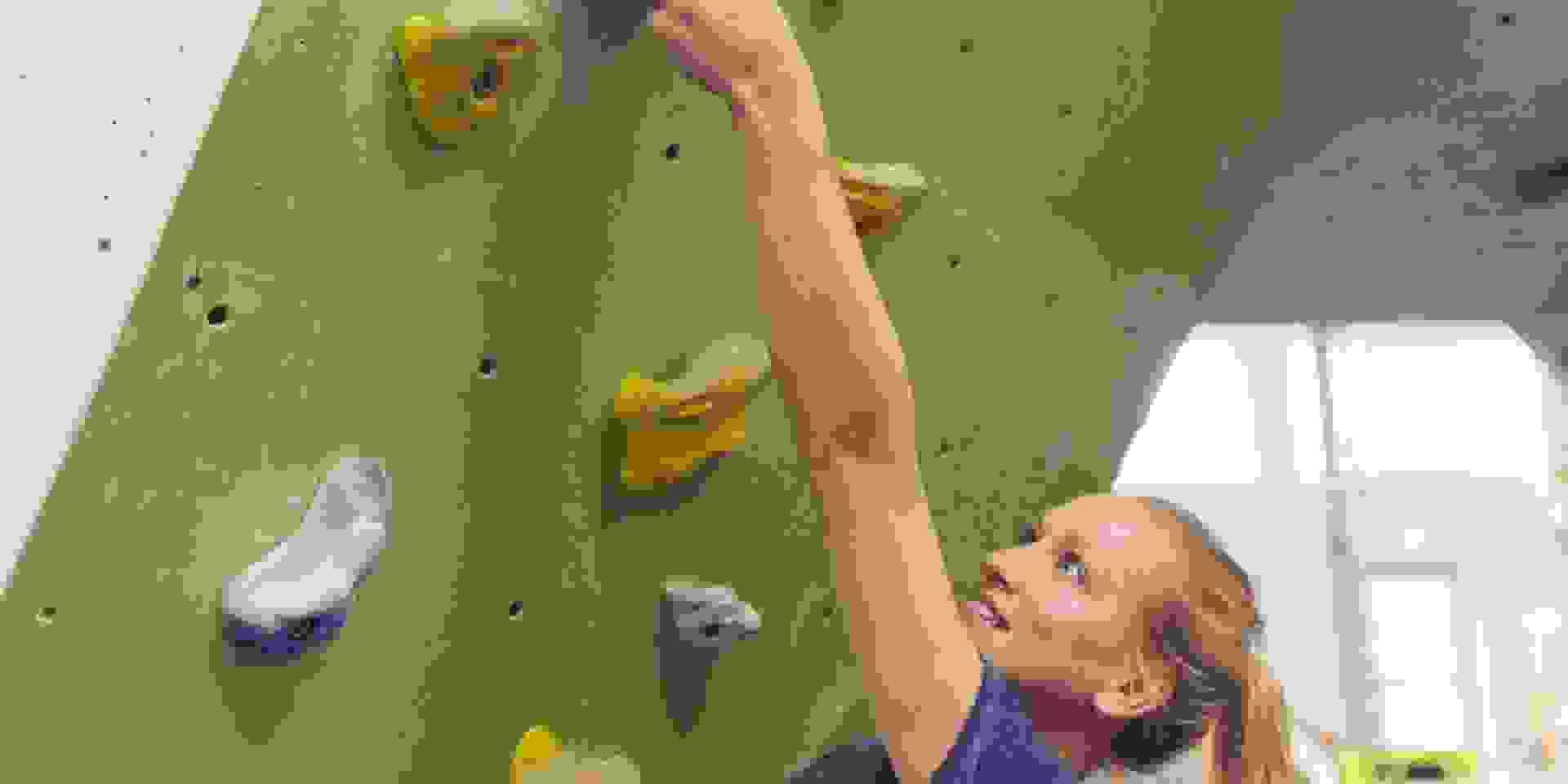Eine Frau hängt an einem Boulderspot mit langem Arm.