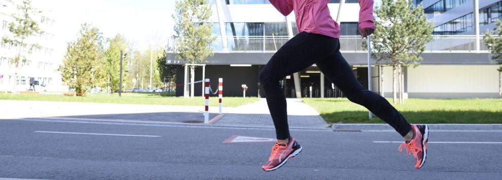 Eine Joggerin läuft in pinken Laufschuhen eine Straße entlang.
