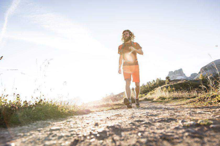 Ein Wanderer spatziert einen Feldweg entlang. Die Sonne im Rücken.