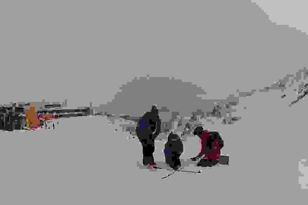 Die Gruppe übt die Feinsuche. Sie bilden mit ihren Skistöcken ein Kreuz und fahren die Linien mit dem LVS Gerät ab.
