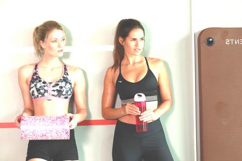 2 Frauen stehen an einer Wand. Eine hält eine große Faszienrolle in der Hand.
