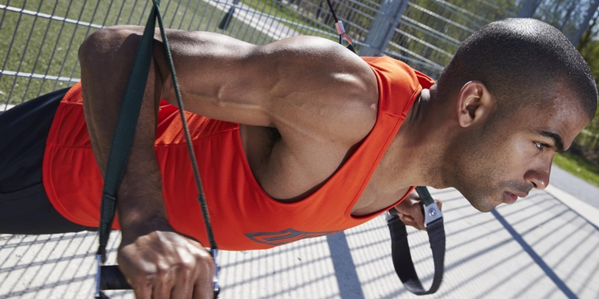 Ein Mann trainiert im freien an einem Schlingentrainer
