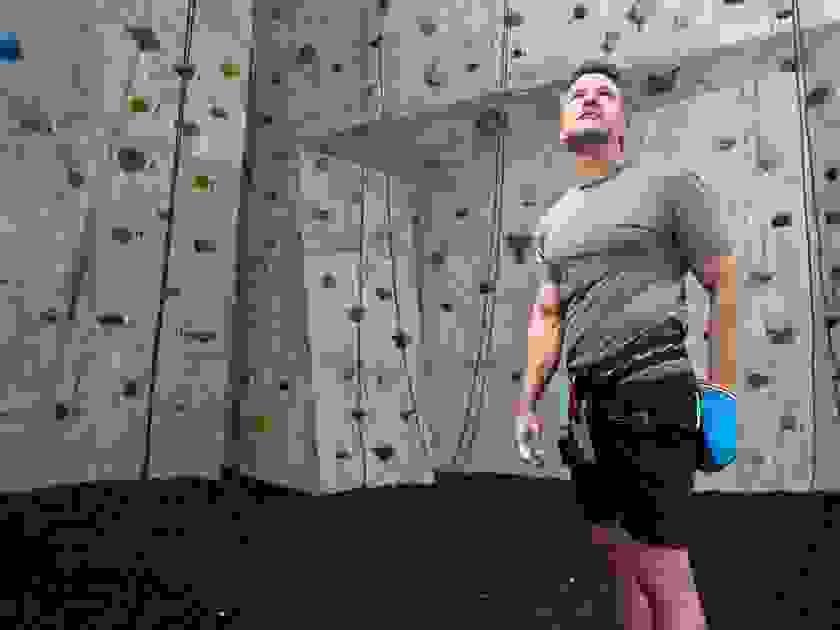 Ein mann in grauem T-Shirt steht in einer Kletterhalle und bereitet sich auf das Wettkampfklettern vor.