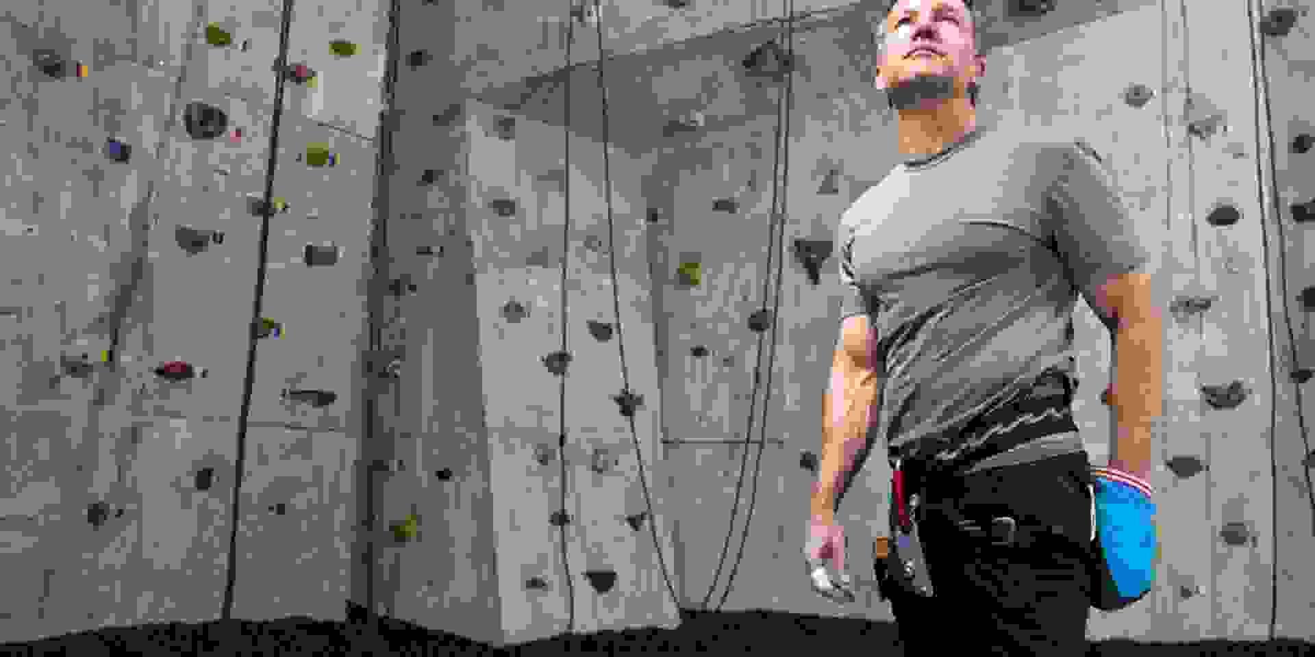 Ein Mann bereitet sich in einer Kletterhalle aufs Wettkapmfklettern vor