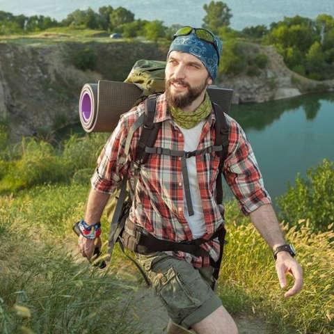Ein Mann mit Bart wandert an einem See entlang. Er trägt ein kariertes Wanderhemd, Rucksack und Kopftuch.