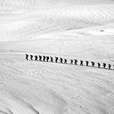 Viele Skitourer gehen in einer Winterlandschaft hintereinander her.