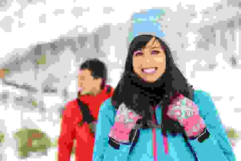Eine Frau steht in blauer Jacke, mit Mütze und Handschuhen in einer Schneelandschaft.