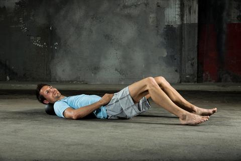 Ein Mann trainiert mit einer Faszienrolle.
