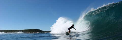 Ein Surfer in Neoprenanzug surft über eine hohe Welle.