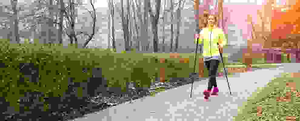 Eine Frau betreibt Nordic Walking in einem Park. Sie geht mit Nordic Walking Stöcken einen Weg entlang.