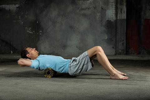 Ein Mann trainiert mit einer Faszienrolle seinen oberen Rücken.