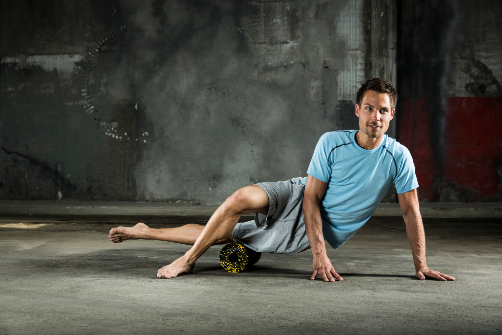 Ein Mann trainiert seinen äußeren Oberschenkel mit einer Blackroll.
