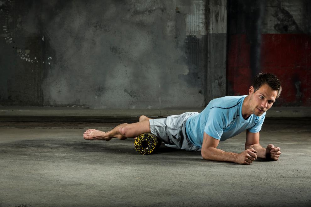 Ein Mann trainiert die Innenseite eines Oberschenkels mit einer Faszienrolle.