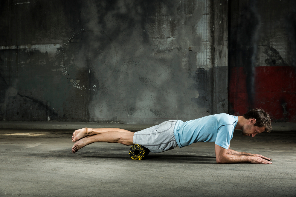 Ein Mann trainiert seinen vorderen Oberschenkel mit einer Faszienrolle.