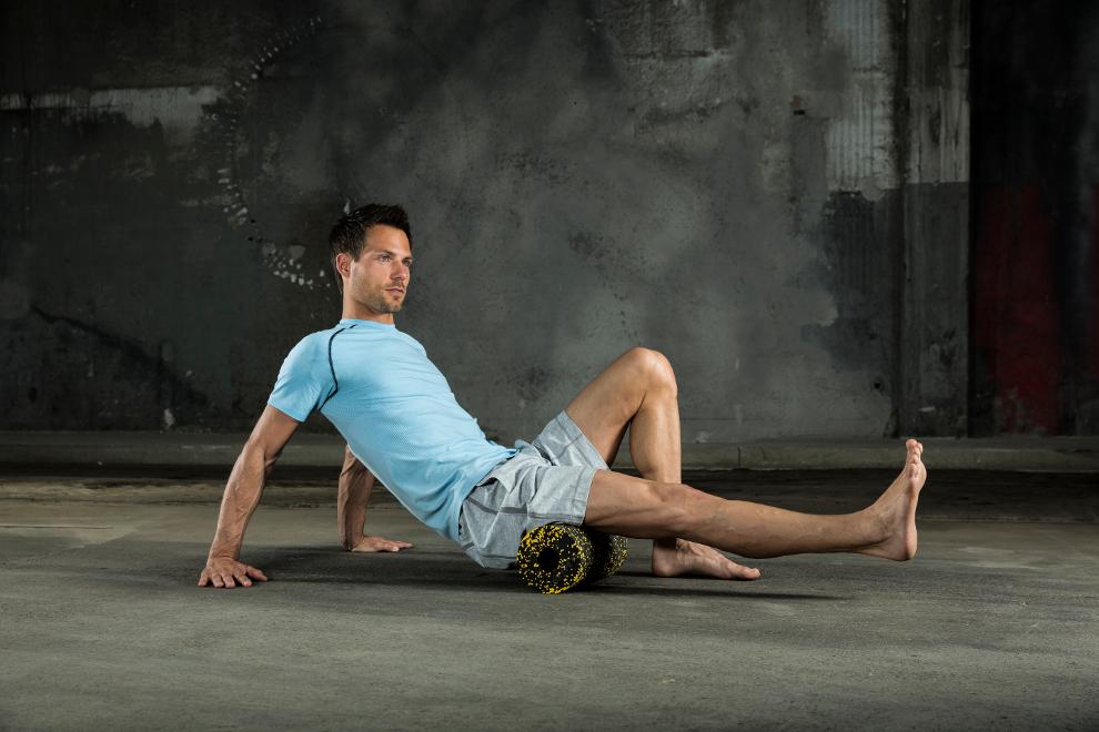 Ein Mann trainiert seinen hinteren Oberschenkel mit Faszienrolle.