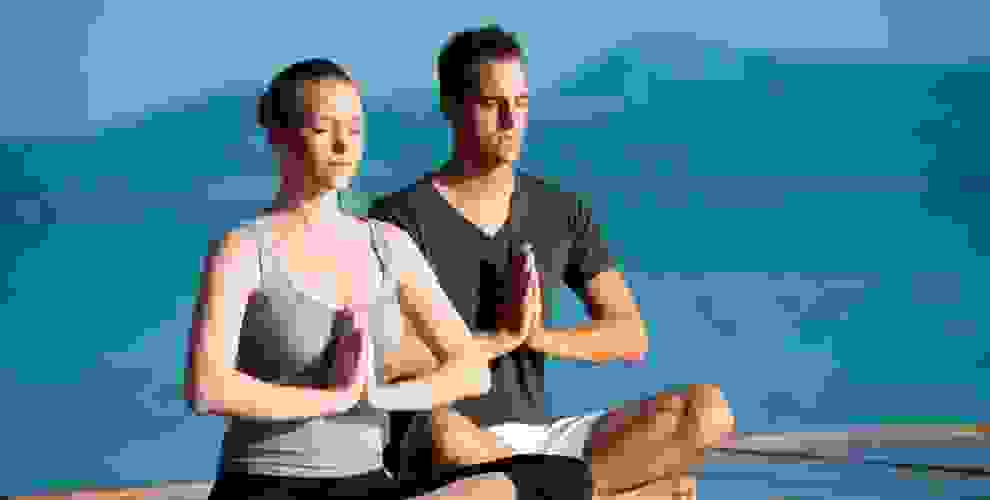Ein Mann und eine Frau beim Yoga in organischer Yoga Kleidung.