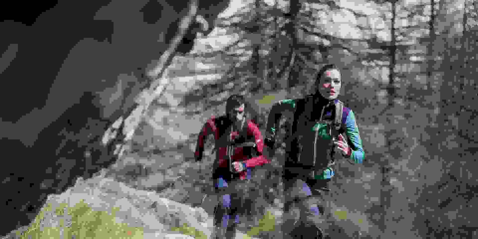 Ein Paar beim Trailrunning am Berg bei Herbstwetter