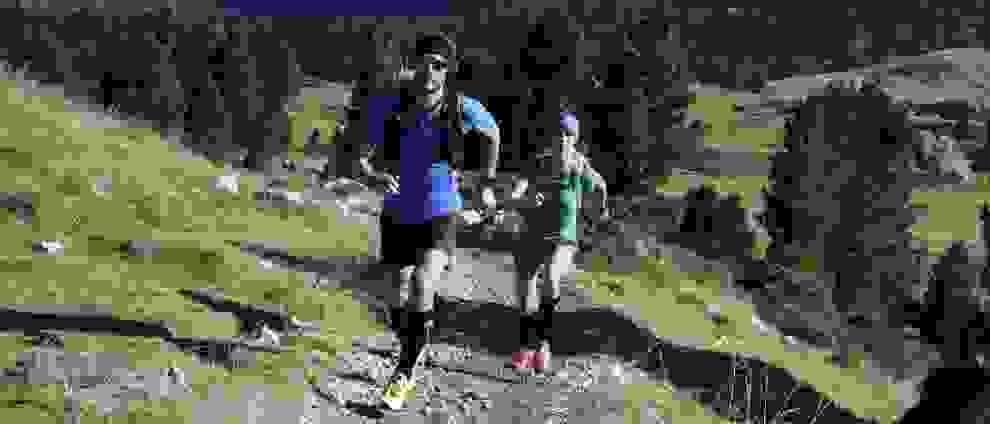 Ein Mann und eine Frau laufen einen Bergpfad hinauf.