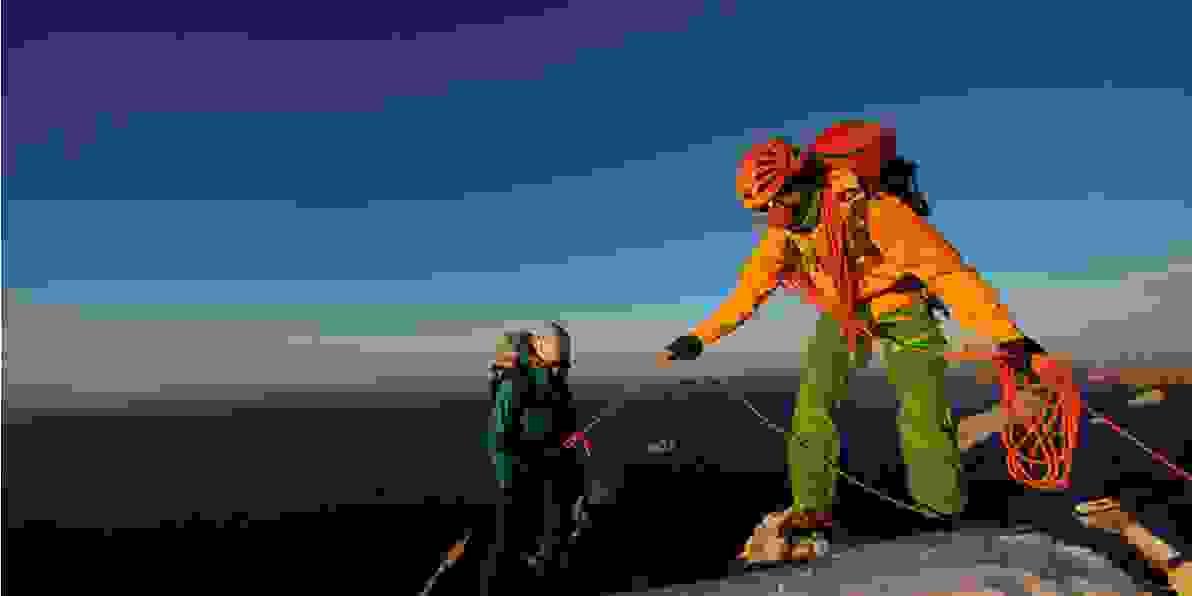 Peter Fresia als Bergführer auf dem Gipfel eines Berges. Er hilft einem anderen Wanderer mit einem Seil hinauf.