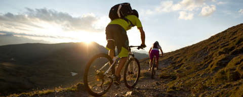 Zwei Mountainbiker fahren durch ein Gebirge. Am Horizont ist ein Sonnenuntergang zu sehen.