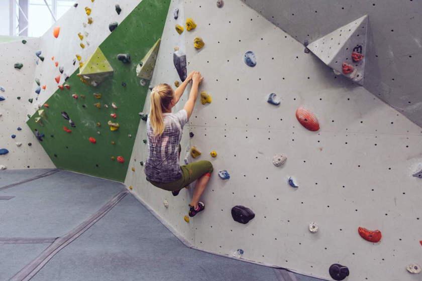 Eine Frau bouldert in einer Kletterhalle und achtet verstärkt auf ihre Beinhaltung.