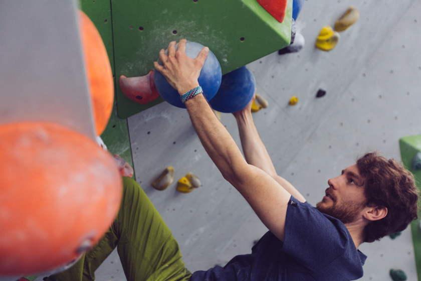 Ein Mann bouldert mit gestreckten Armen.