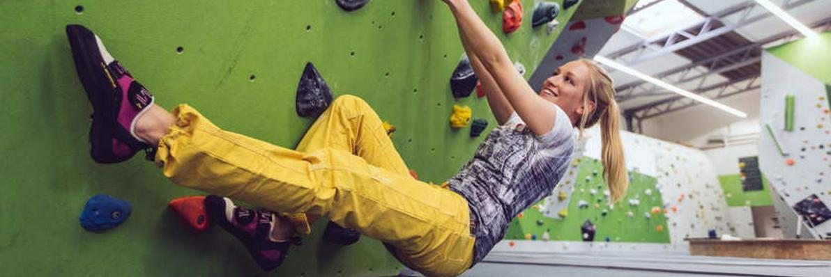 Eine Frau demonstriert an einer Boulderwand wie man den Körperschwerpunkt beim Bouldern richtig setzt.