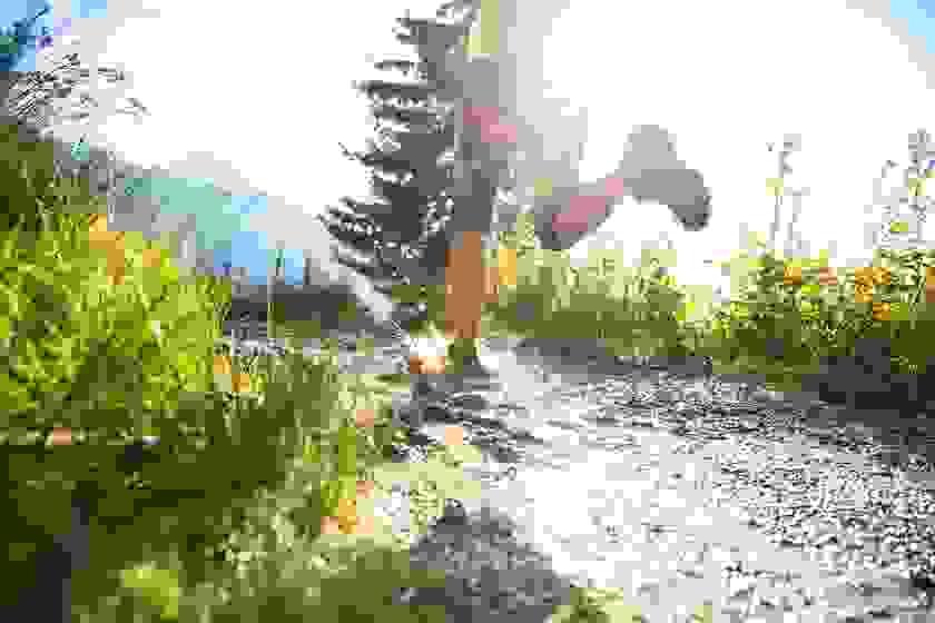 Der Salomon Speedcross GTX 3 getragen von einer Frau, die in einem seichten Fluss läuft.