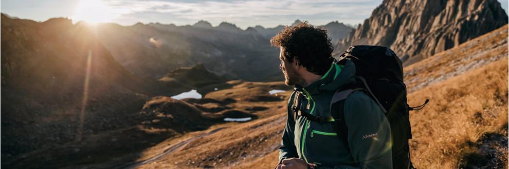Ein Mann steht auf einem Berg und trägt eine Schöffel Zipin Jacke und schaut auf die untergehende Sonne.