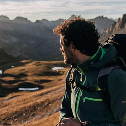 Eine Mann steht auf einem Berg bei Sonnenuntergang.