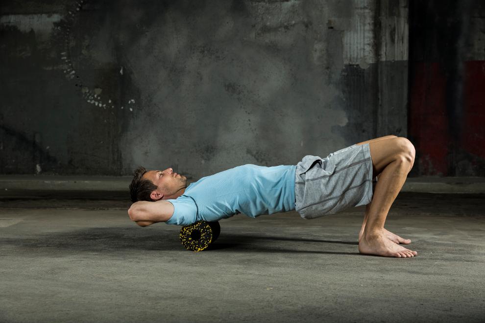 Ein Mann zeigt, wie man mit einer Blackroll Schulterverspannungen löst.