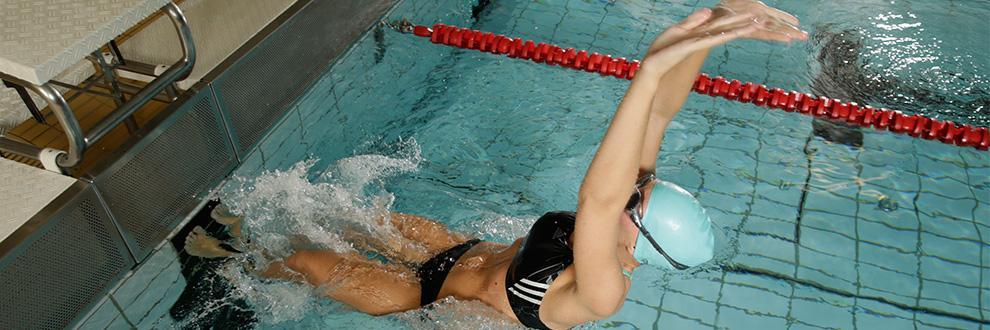 Eine Schwimmerin stößt sich mit den Füßen vom Beckenrand ab um schneller Geschwindigkeit beim schwimmen aufnehmen zu können.
