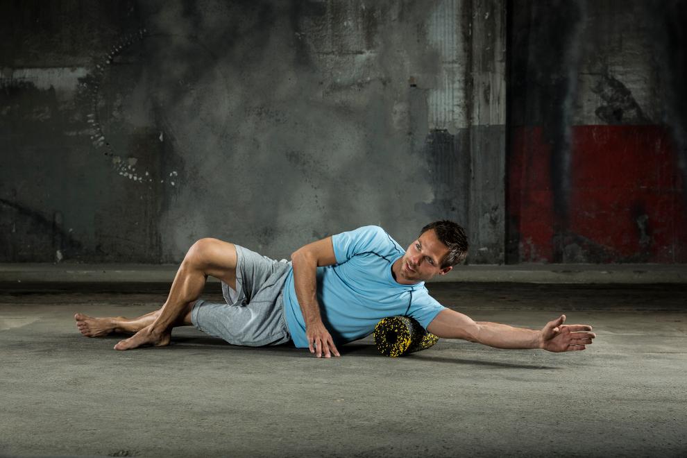 Ein Mann trainiert seine seitliche Brustmuskulatur mit einer Faszienrolle.