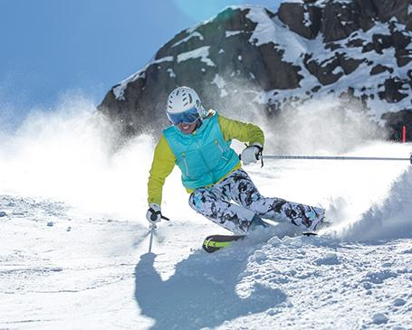 Ein Skifahrer rast die Piste hinab.