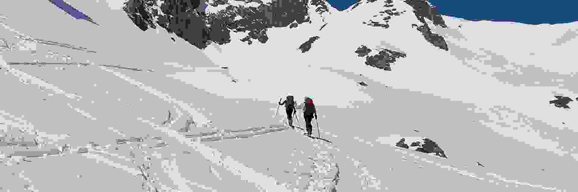 2 Skitourer in einer weiten Schneelandschaft unterwegs.