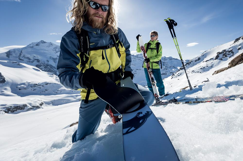 Ein Mann und eine Frau in voller Skitourenbekleidung auf einem Berg.