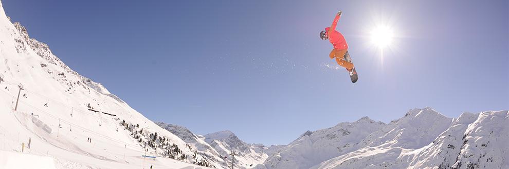 Ein Snowboarder springt auf seinem Snowboard weit in die Luft. Im Hintergrund ist ein strahlend blauer Himmel zu sehen und die Sonne strahlt auf die Schneelandschaft hinab.