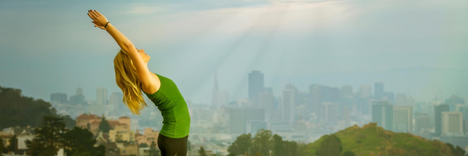 Eine Frau macht die Yogaübung Sonnengruss.