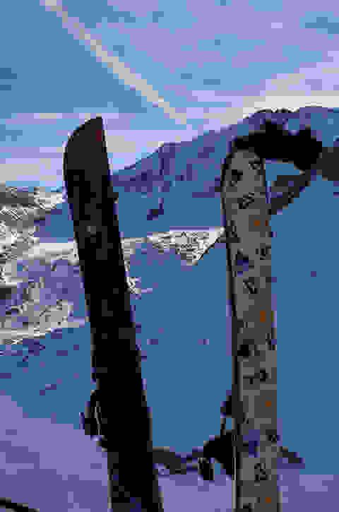 2 Splitboards stecken hochkant im Schnee. Sie sind jeweils mit einem Fell überzogen.