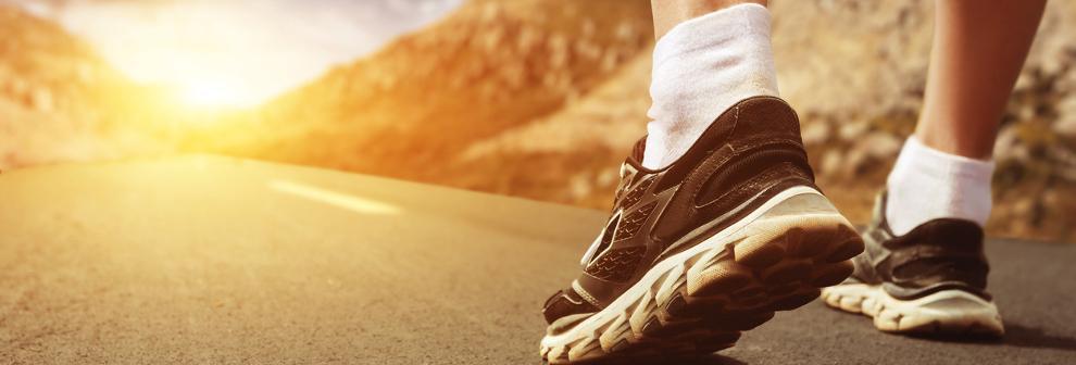 Ein Fuß, der in weißen Sportsocken und schwarzen Laufschuhen steckt.