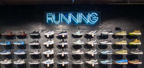 Übersicht Laufschuhe von verschiedenen Marken und Laufschuh Typen in einer SportScheck Filiale.