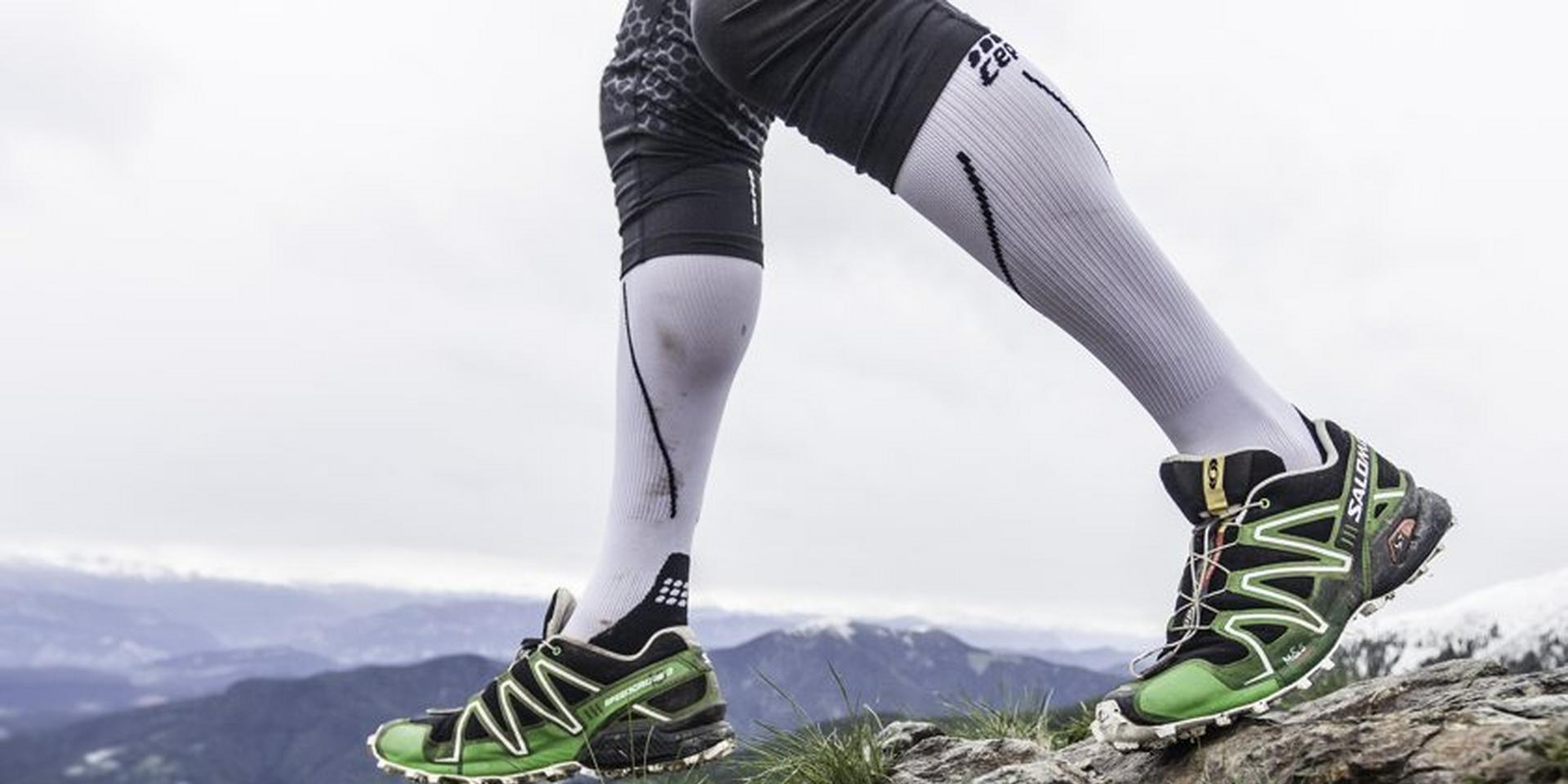 Die Beine eines Trailrunners der Kompressionssocken trägt