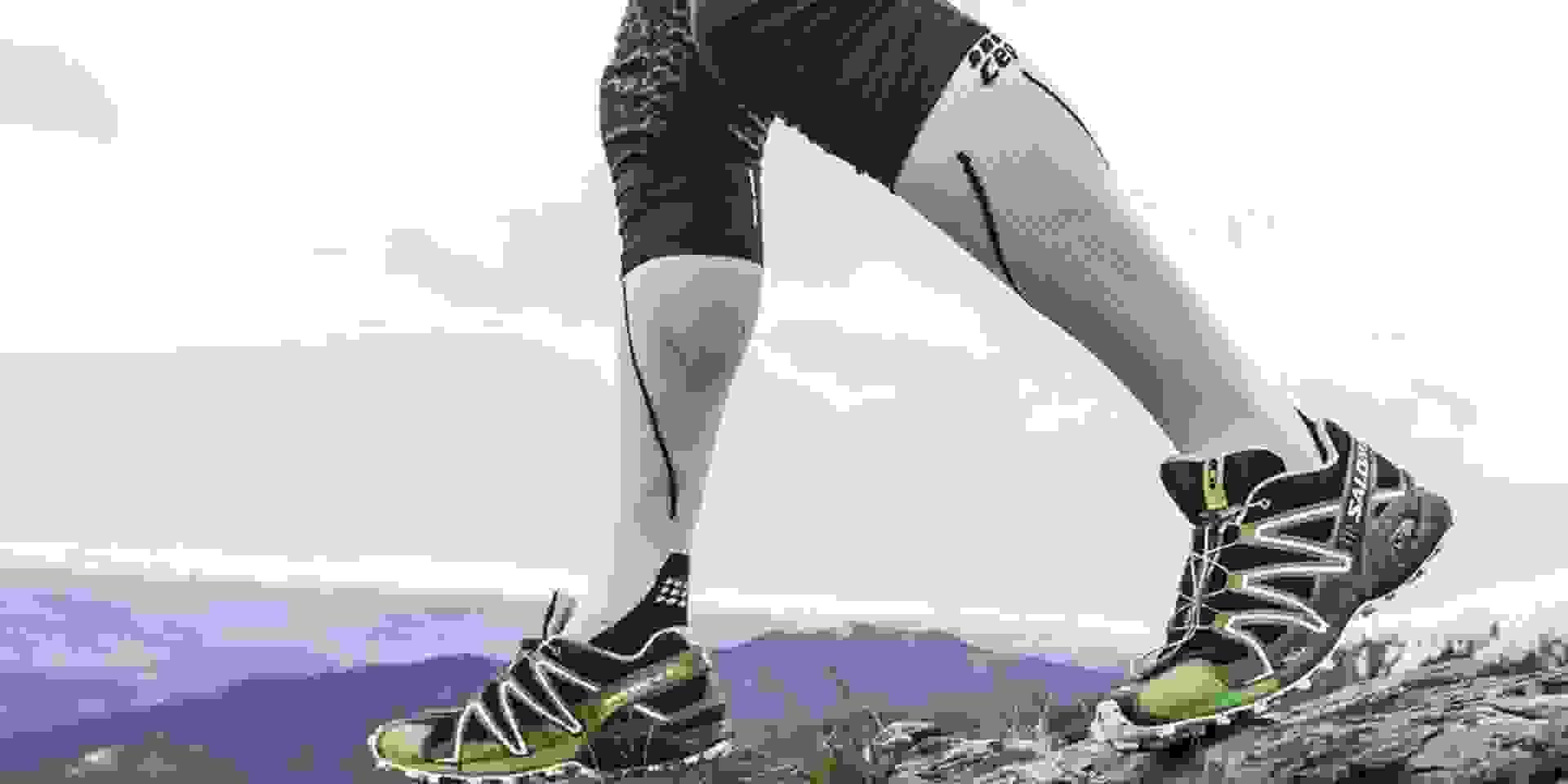 Ein Trailrunner mit weißen Kompressionssocken läuft einen Bergpfad hinauf.