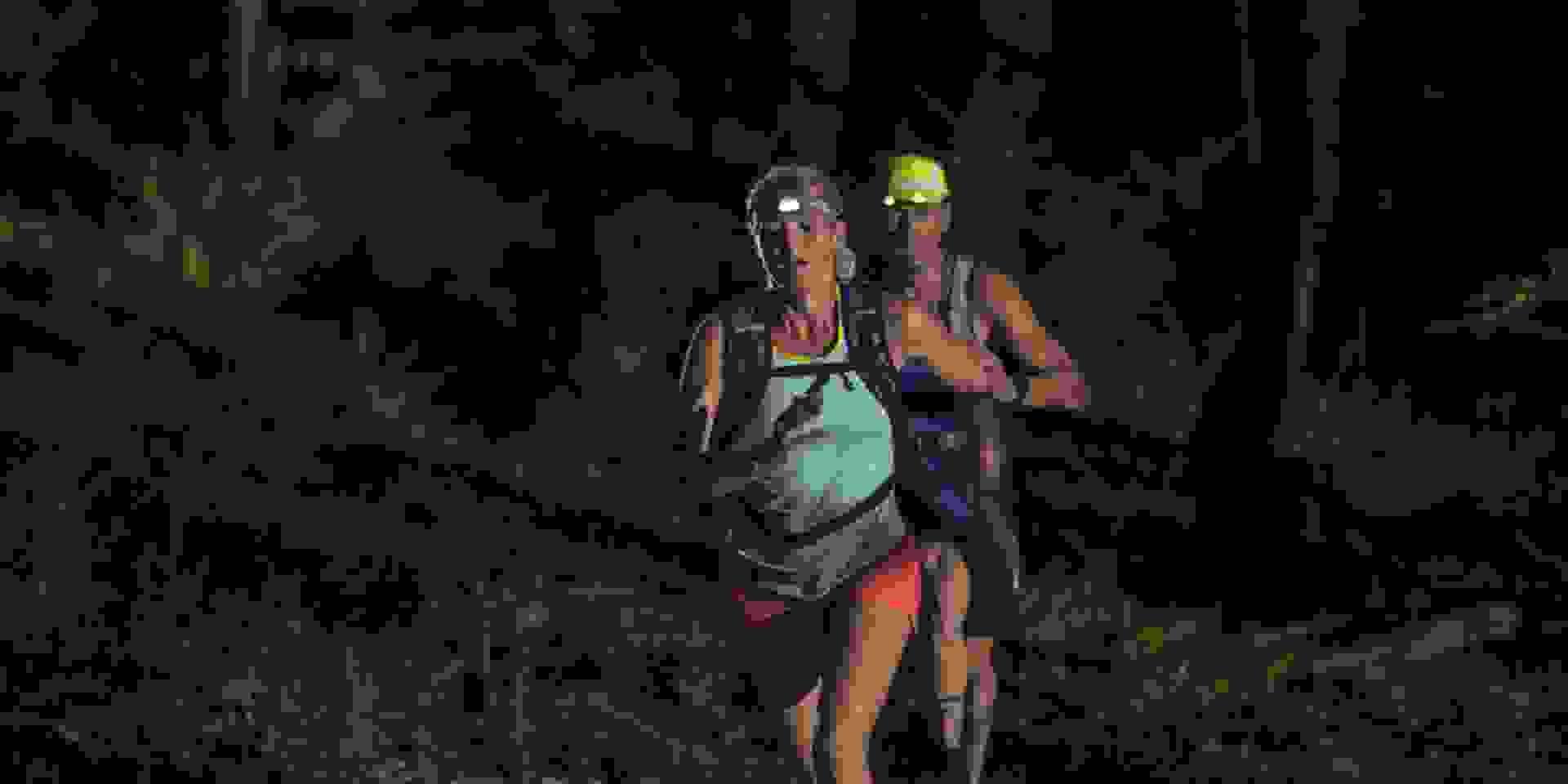 2 Trailrunner während des Laufens von vorne im Dunkeln fotografiert.