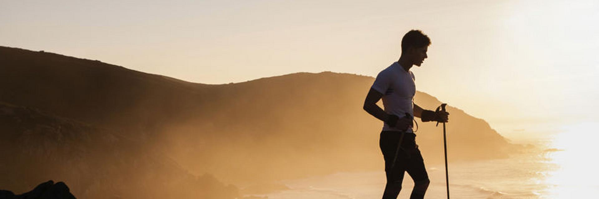 Ein Trailrunner steht mit Trailrunning Stöcken in der Hand während eines Sonnenuntergangs auf einer Anhöhe.