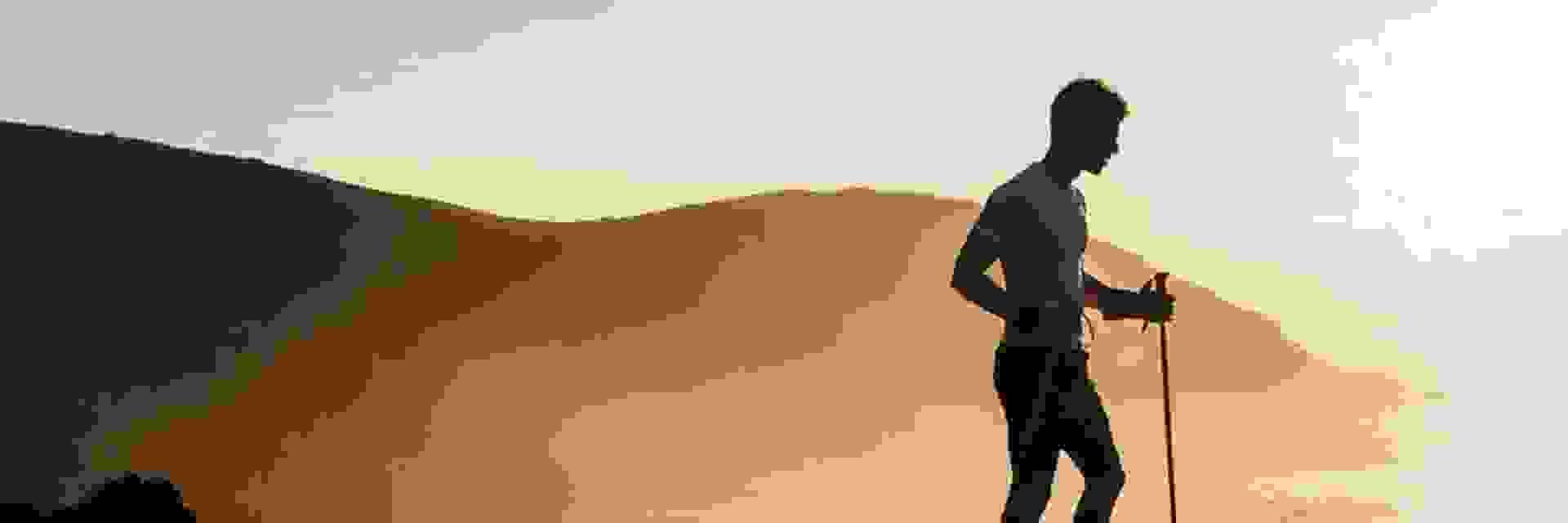 1 Wanderer ist in der Dämmerung am Meer unterwegs.