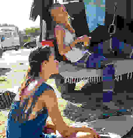 2 Frauen entspannen in der Sonne. Eine sitzt auf dem Boden, die andere im Kofferaum eines Autos.
